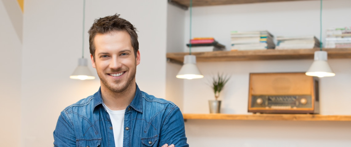 Young man with stubble, wearing a denim shirt, looking relaxed and positive in his apartment.