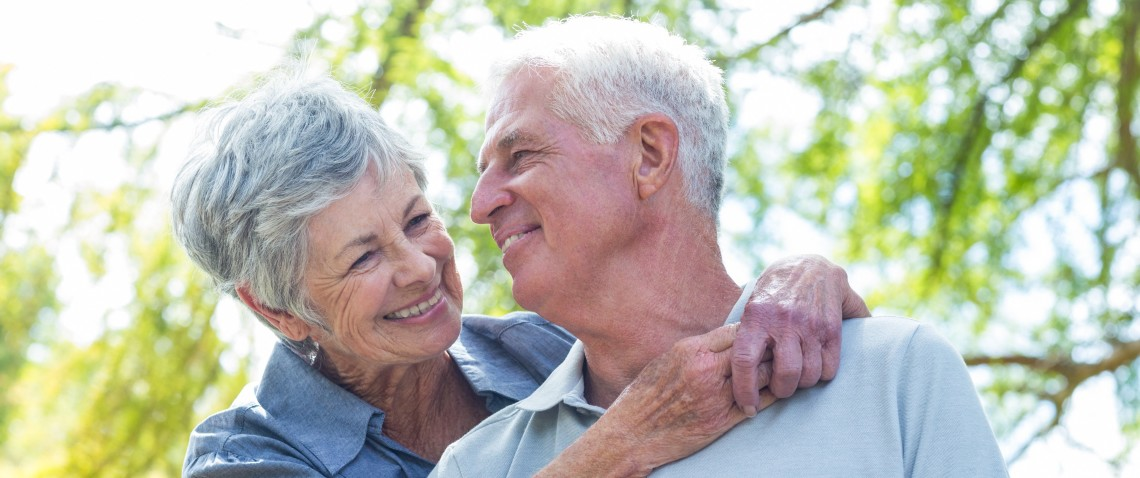 Elderly couple with grey hair, look supportive and lovingly at each other, embracing near a tree.