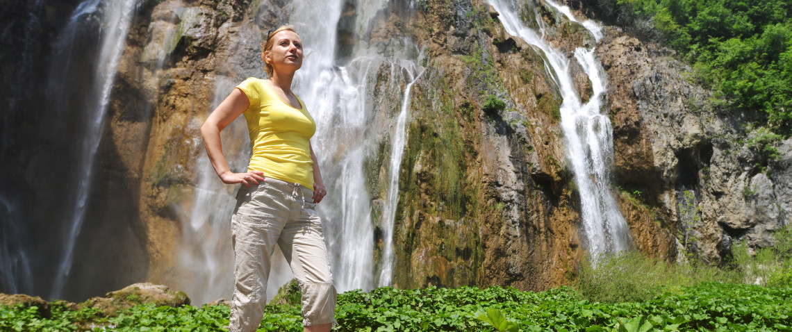 Young fit female in yellow sleeveless top, stood in front of waterfall, after enjoyable walk.