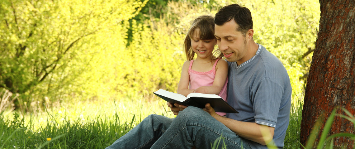 Man reading a book to his young daughter, with his arm around her, sat in the sun beneath a tree.