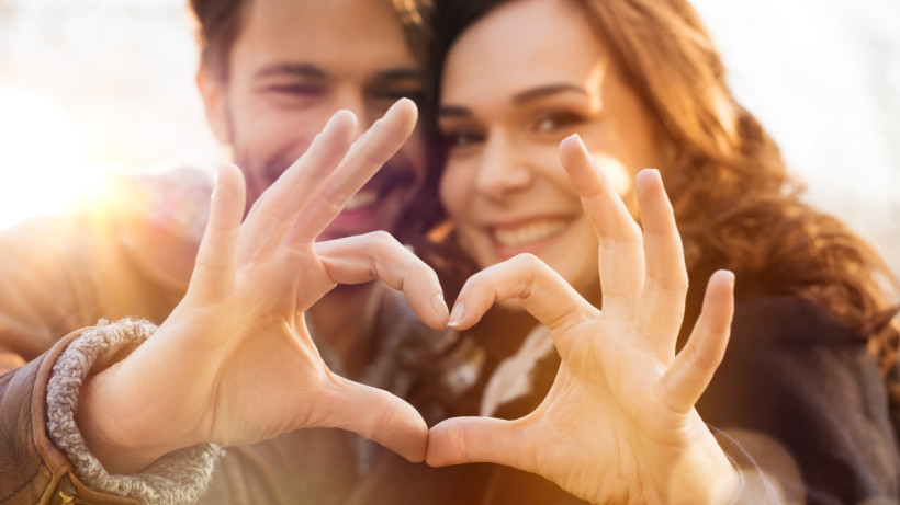 Young couple, look happy and harmonious as they create a heart shape with their fingers and thumbs.