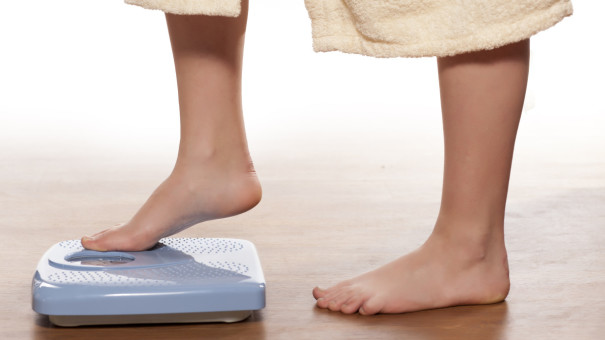 Woman in long bathrobe, barefoot with one foot half way stepping onto weighing scales.
