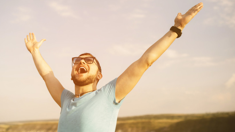 Young man with glasses, throwing arms up into the air and looking up to the sky with confidence.