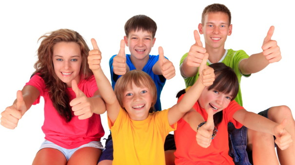 Two adolescent teenagers and three younger children in bright plain tee-shirts, showing thumbs up and big smiles.